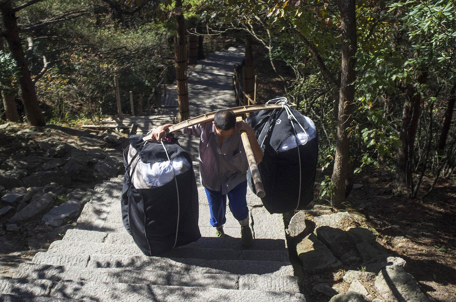 Man carrying tourists' bags.