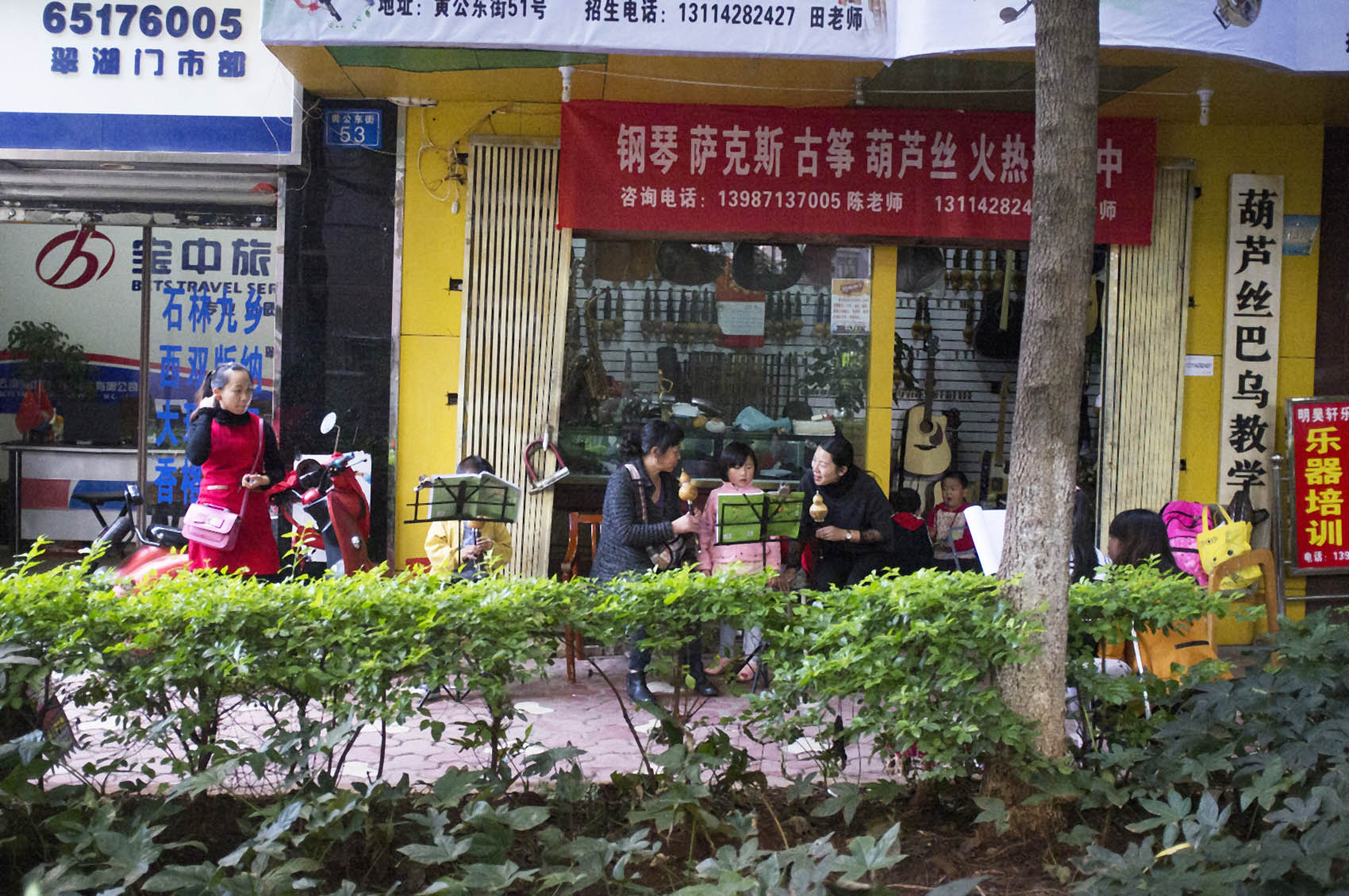 Children practice playing traditional instruments on the street.
