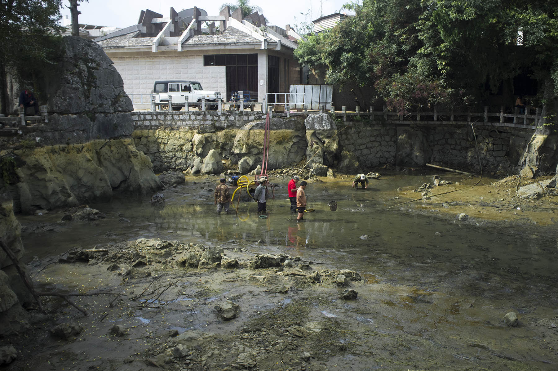 Workers draining the pond.