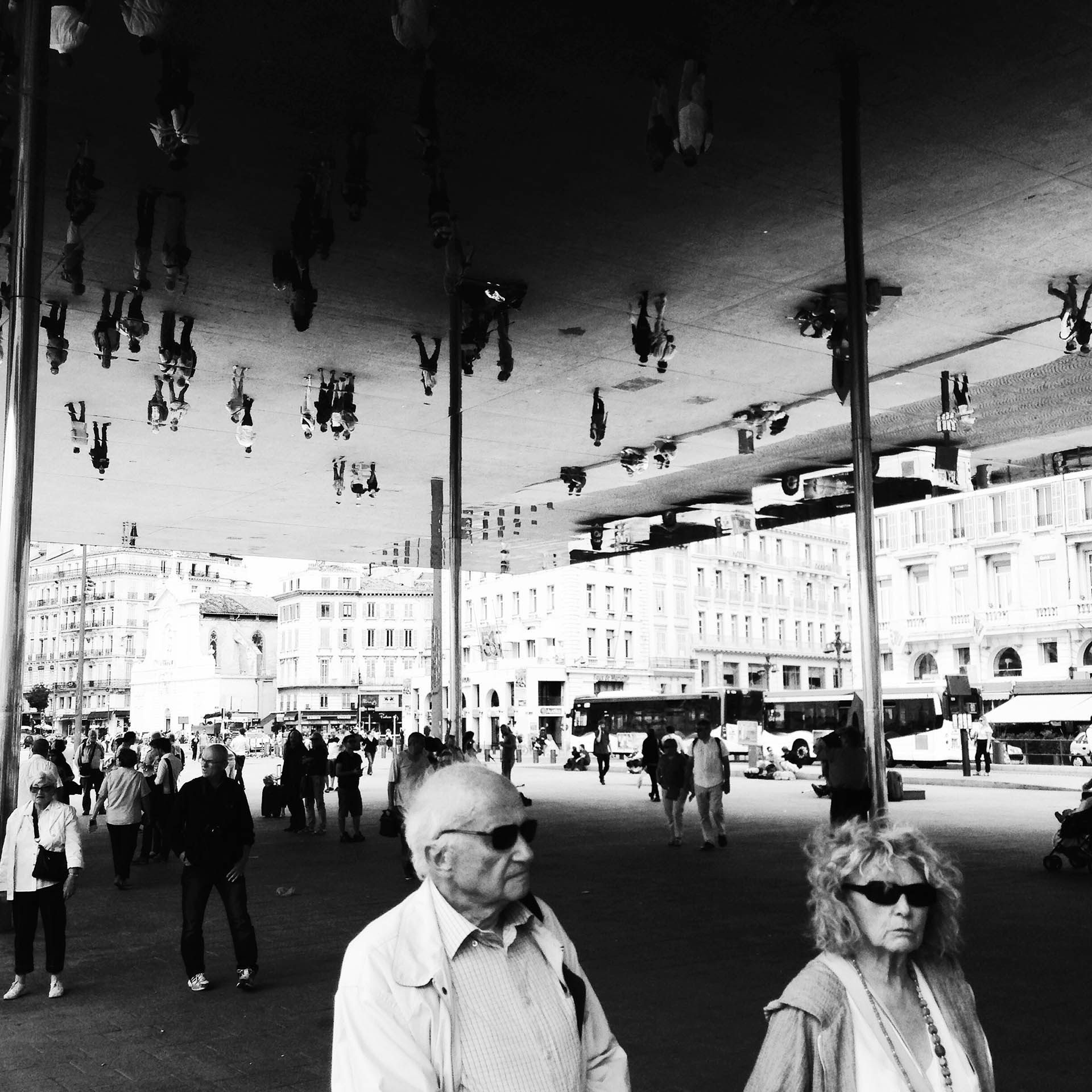 A polished steel canopy reflects visitors walking underneath in Marseille's harbour.
