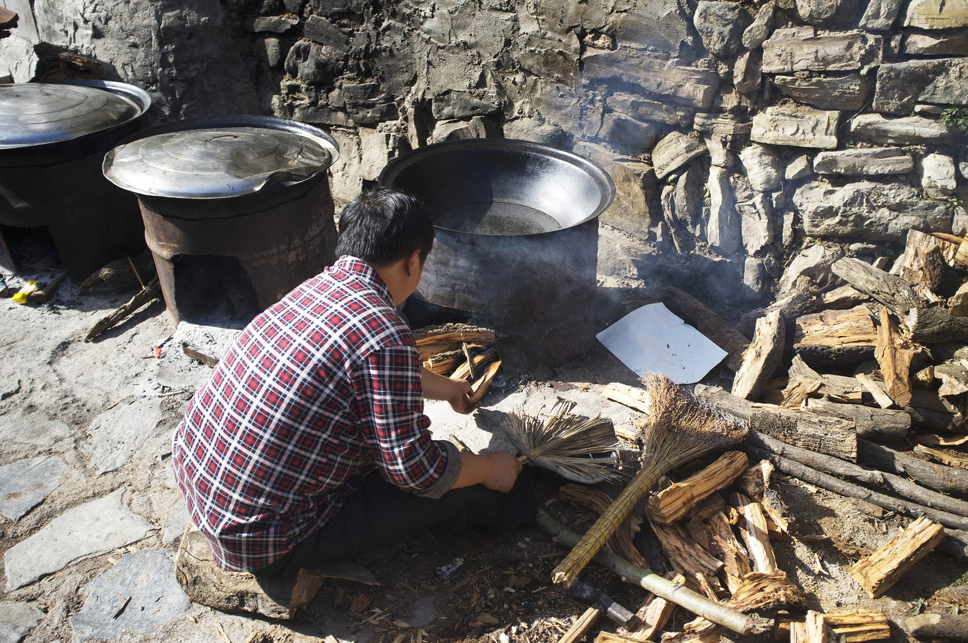 A man is getting the fire ready to make street food.