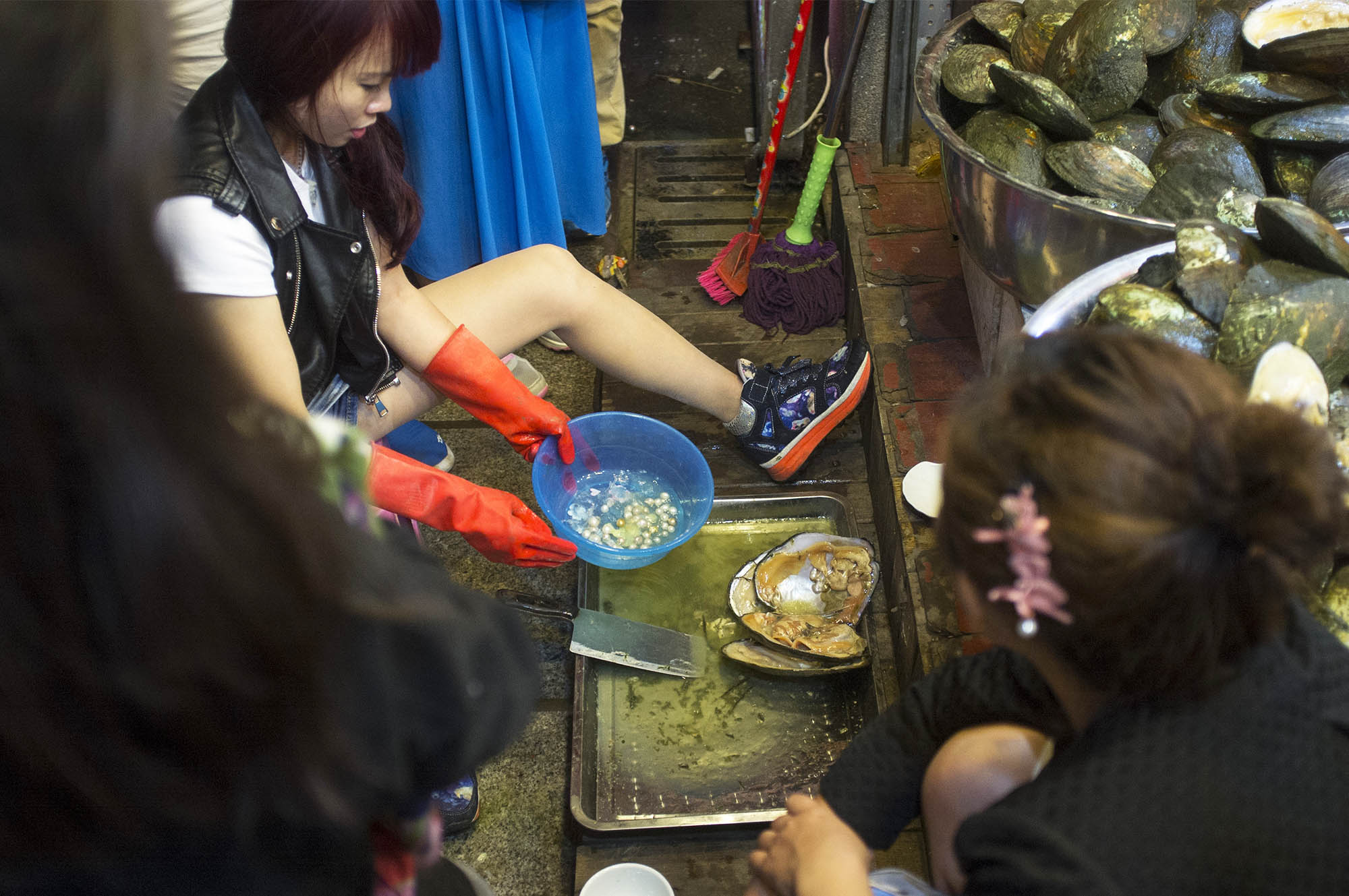 A shop owner is entertaining tourists by shelling mollusks.