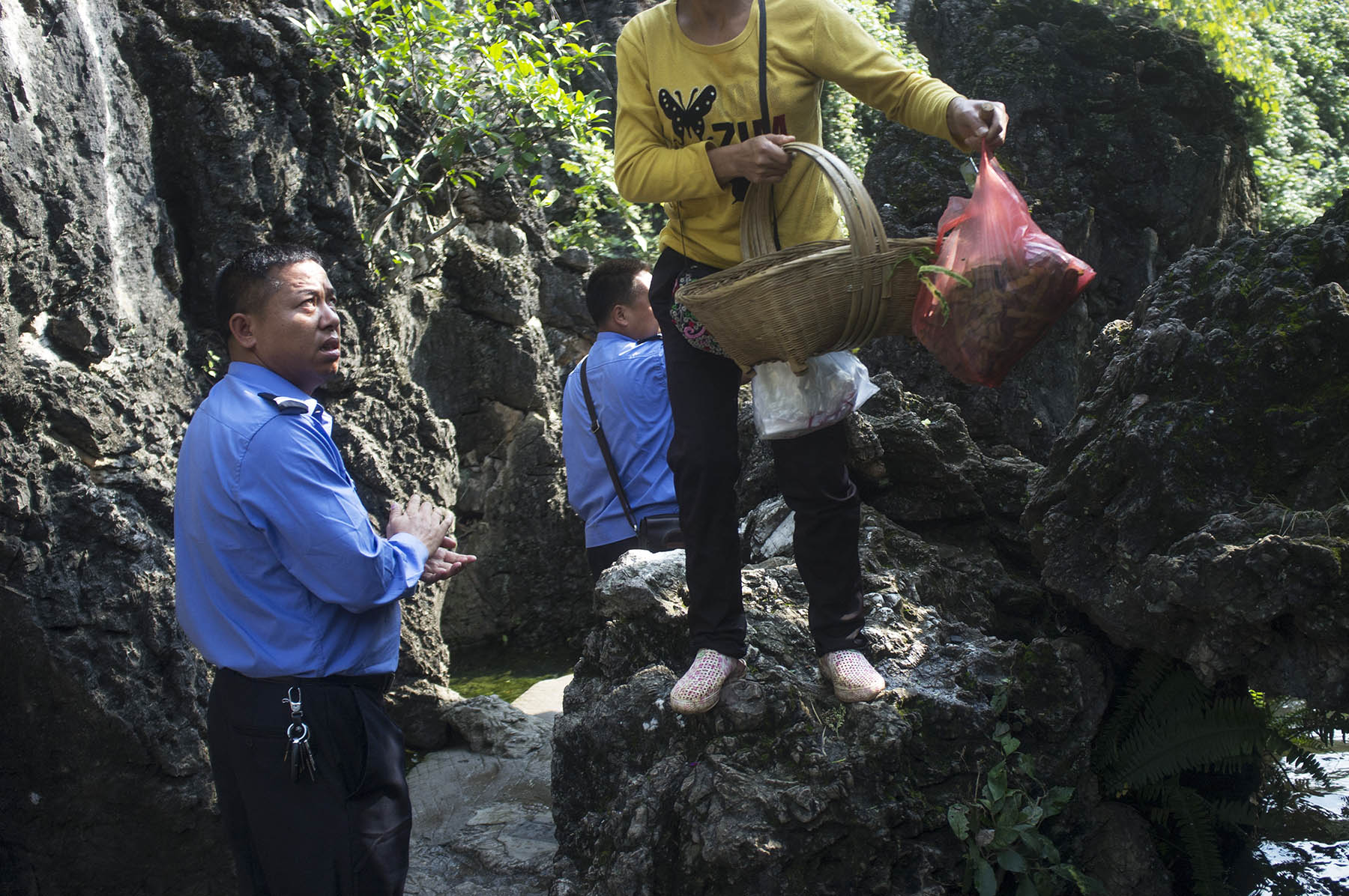 A security representative cleans his hands of the cucumbers he confiscated and threw away in the river, while a woman tries to step off the rock with an empty basket and bag of cucumber skins.