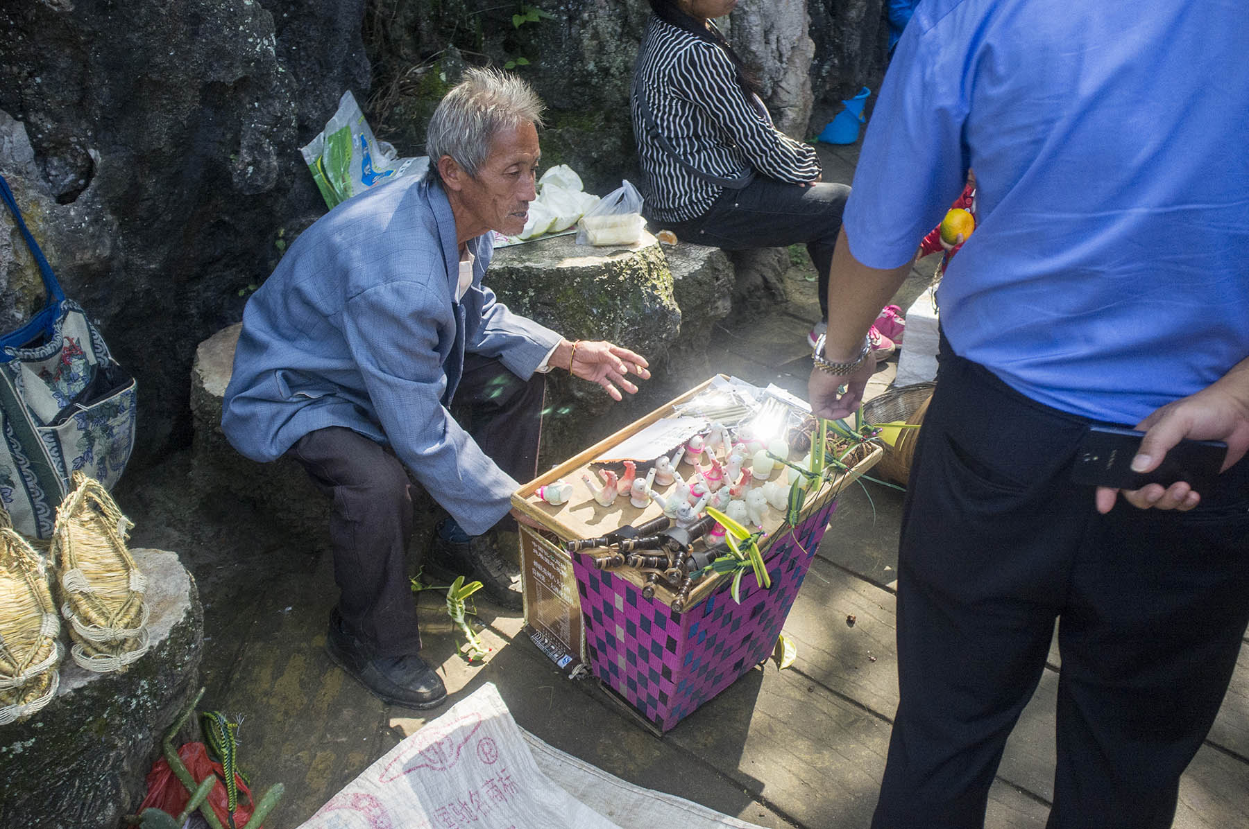 An old man is caught hiding illegal souvenirs under a plastic cover, he is hiding the most valuable things inside the basket.