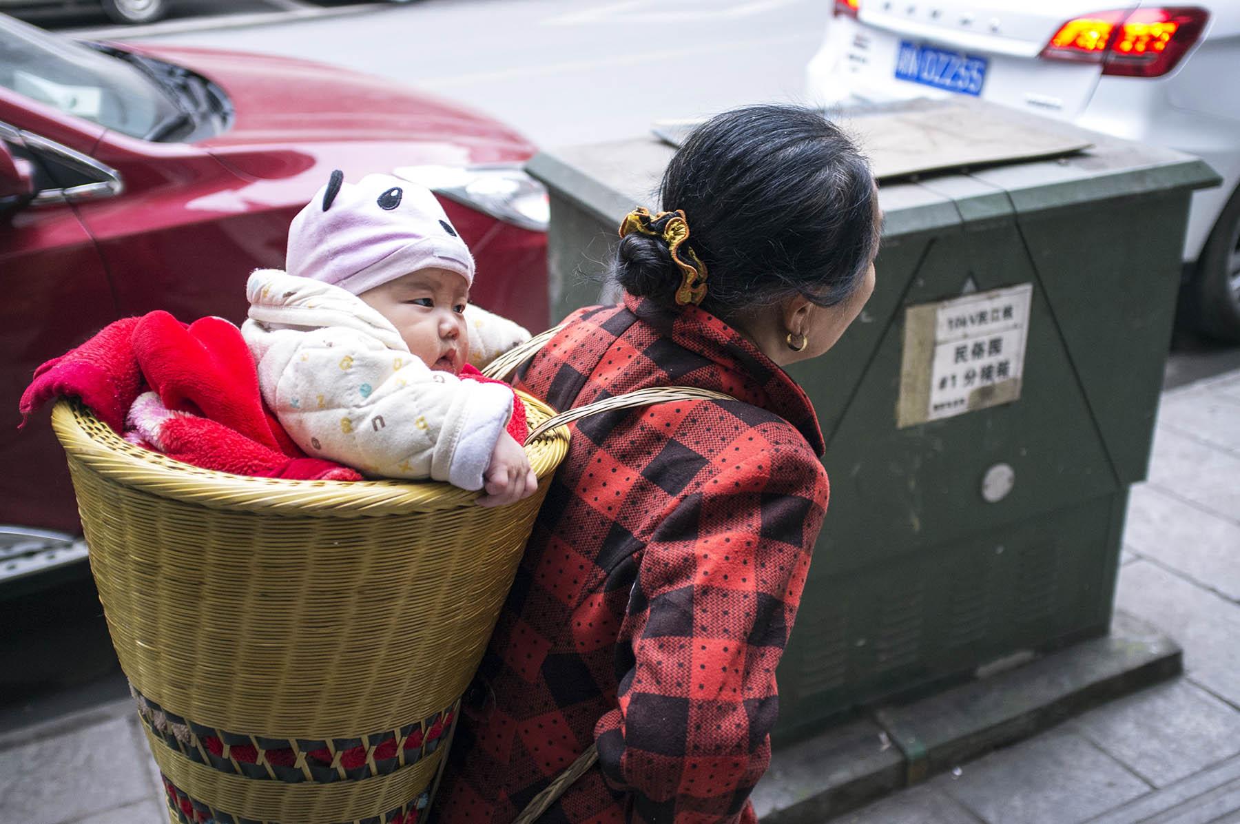 Grandma is carrying her grandson.