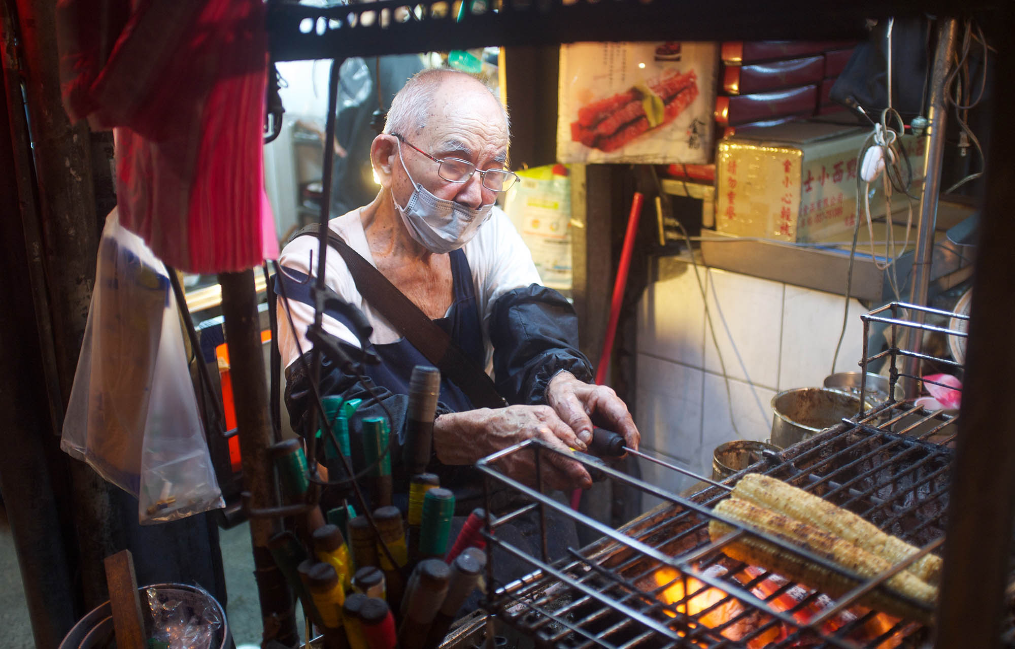 Owner of the stall grills corn and sausages.