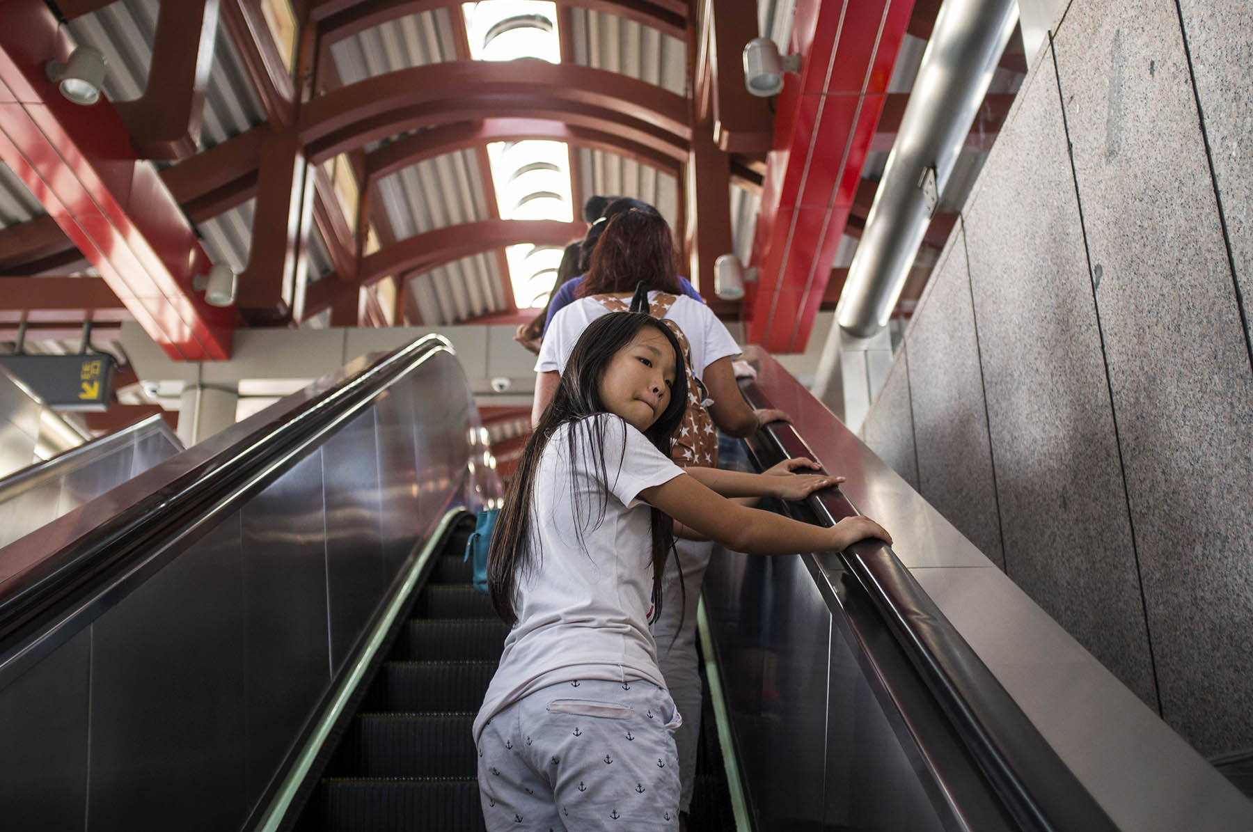 """There is so much clothing business in Taipei, that even metro women's voice on stops says """"doors clothing"""". Girl on the escalator."""